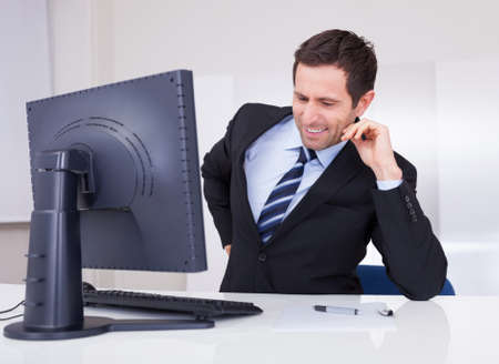 Portrait Of Happy Businessman Using Computer At Workplace photo