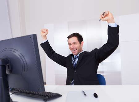 happy young man: Portrait Of Happy Businessman Cheering At Workplace Stock Photo