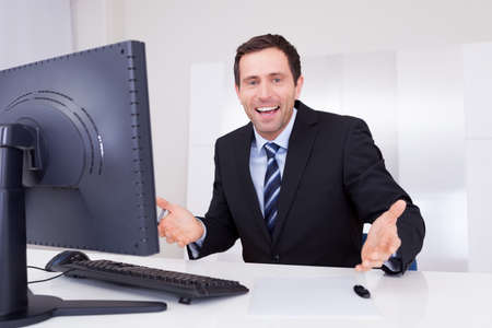 Portrait Of Happy Businessman Cheering At Workplace Stock Photo - 15403701