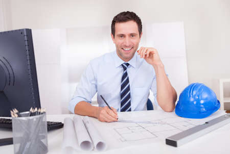 ingeniero civil: Retrato del arquitecto con Blueprint En La Oficina