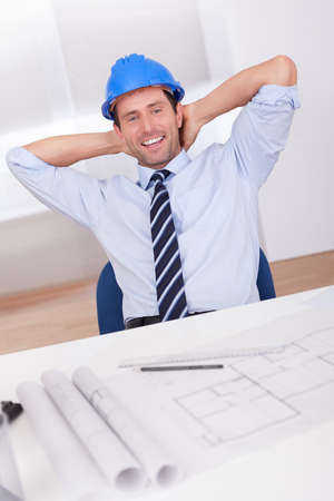 people from behind: Portrait Of Architect Relaxing With Blueprint In The Office