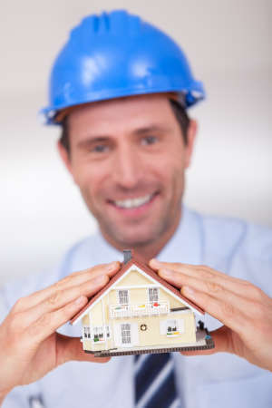dwelling: Portrait Of A Cheerful Architect Holding A House Model Stock Photo