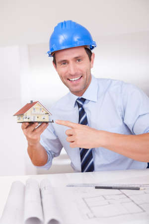 Portrait Of A Cheerful Architect Holding A House Model Stock Photo - 15403715