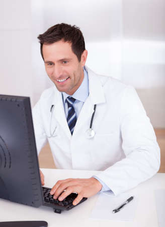 consultant physicians: Smiling Medical Doctor With Stethoscope Sitting At A Desk Stock Photo