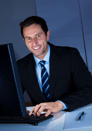 Portrait Of Happy Businessman Using Computer At Workplace Stock Photo - 15404293