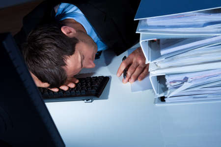 overburdened: Tired Businessman Sleeping At Workplace In The Office Stock Photo