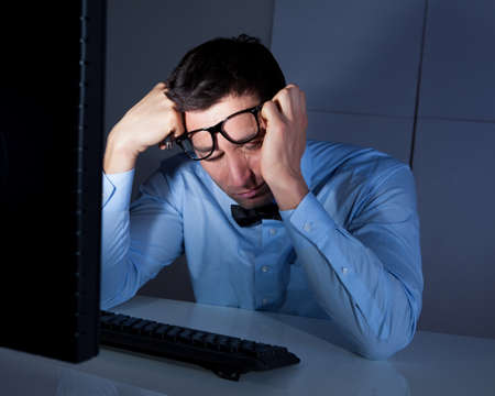 bored man: Tired Businessman Sleeping At Workplace In The Office Stock Photo
