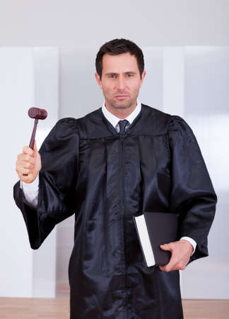 adjourned: Portrait Of A Serious Male Judge Holding The Gavel And Book