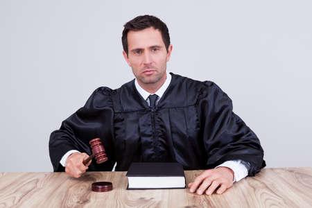 frase: El juez en una corte masculino golpeando el martillo