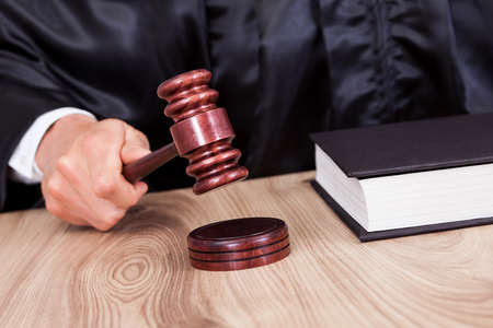 the litigation: Male Judge In A Courtroom Striking The Gavel