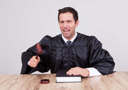 Male Judge In A Courtroom Striking The Gavel Stock Photo - 15404143