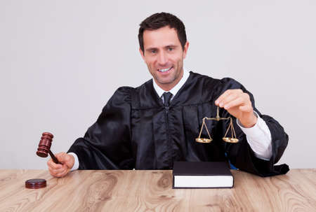 arbitrate: Male Judge Holding Gavel and Scale In Courtroom