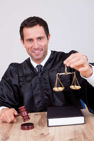Male Judge Holding Gavel and Scale In Courtroom Stock Photo - 15404324