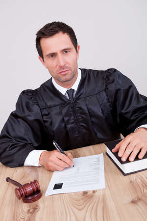 Male Judge Writing On Paper In Courtroom Stock Photo - 15404179