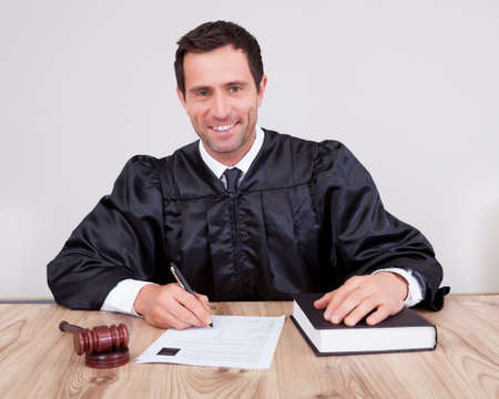 Male Judge Writing On Paper In Courtroom Stock Photo - 15404115