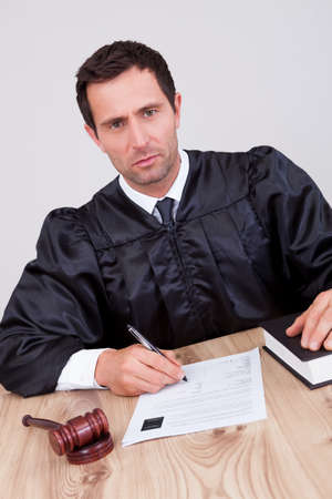 Male Judge Writing On Paper In Courtroom Stock Photo - 15404270