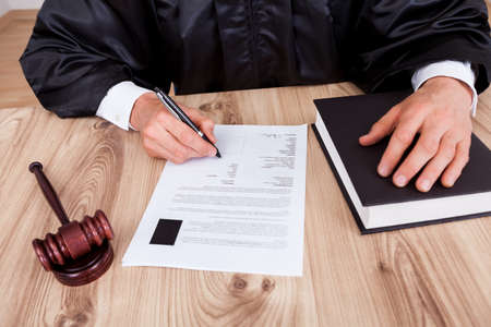 Male Judge Writing On Paper In Courtroom Stock Photo - 15388037