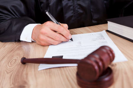 signing authority: Male Judge Writing On Paper In Courtroom