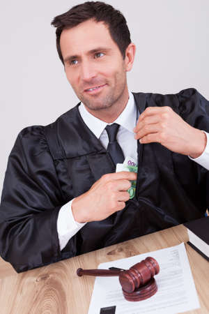 putting money in pocket: Male Judge Putting Some Money In His Pocket In A Courtroom