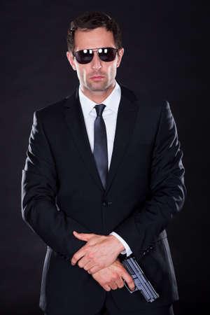 pistole: Ritratto di giovane uomo con pistola su sfondo nero