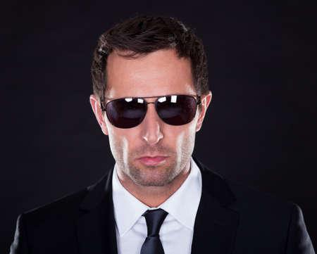 garde du corps: Portrait De Jeune Homme Avec Lunettes De Soleil Sur Fond Noir