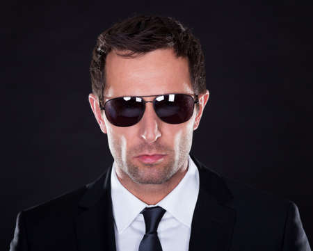 body guard: Portrait Of Young Man  With Sunglasses On Black Background Stock Photo