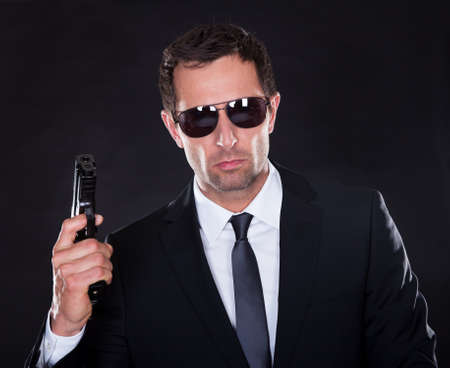 body guard: Portrait Of Young Man With Gun On Black Background