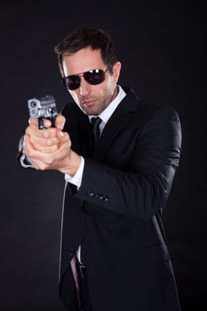 garde du corps: Portrait de jeune homme avec arme � feu sur fond noir Banque d'images