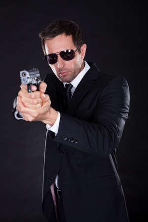 hombre disparando: Retrato de hombre joven con pistola sobre fondo Negro Foto de archivo