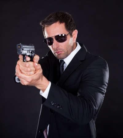 agent de sécurité: Portrait De Jeune Homme Avec Gun Sur Fond Noir Banque d'images