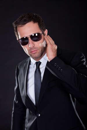 Portrait des jungen Mannes mit Kopfhörer auf schwarzem Hintergrund