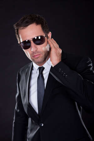 secret agent: Portrait Of Young Man With Earphone On Black Background