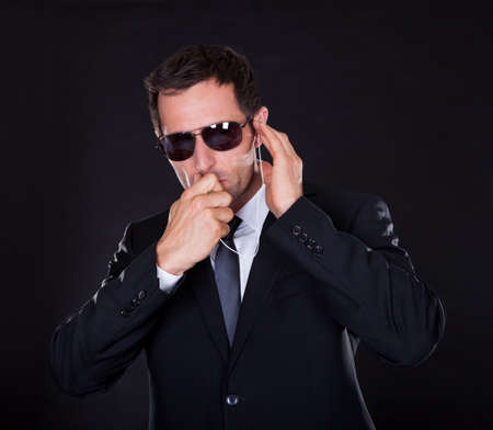 agente: Ritratto di giovane uomo con auricolare su sfondo nero