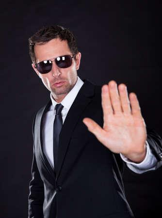 Portrait Of Young Man making stop gesture isoliert auf schwarzem Hintergrund Standard-Bild