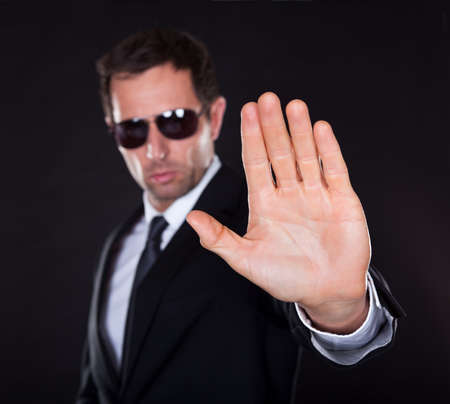 agents: Portrait Of Young Man Making Stop Gesture Isolated On Black Background