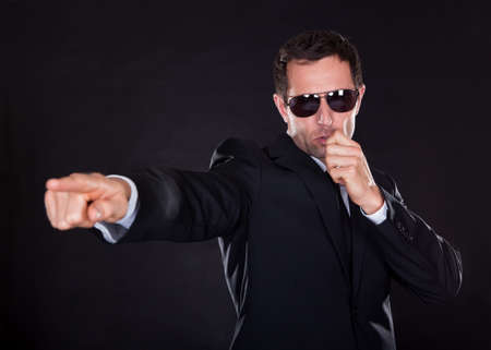 angry businessman: Portrait Of Young Man Points A Finger Isolated On Black Background Stock Photo