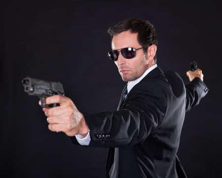 guardaespaldas: Retrato de hombre joven con pistola En Fondo Negro