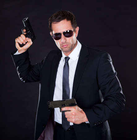 military man: Portrait Of Young Man With Gun On Black Background