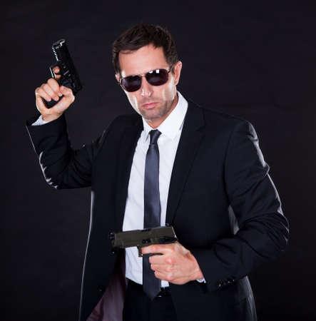 handgun: Portrait Of Young Man With Gun On Black Background
