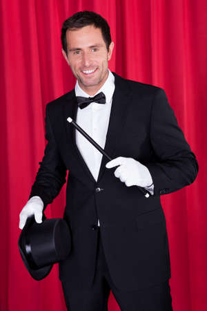 A Magician In A Black Suit Holding An Empty Top Hat And Magic Wand photo