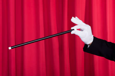magic hat: A Magician In A Black Suit Holding An Empty Top Hat And Magic Wand Stock Photo