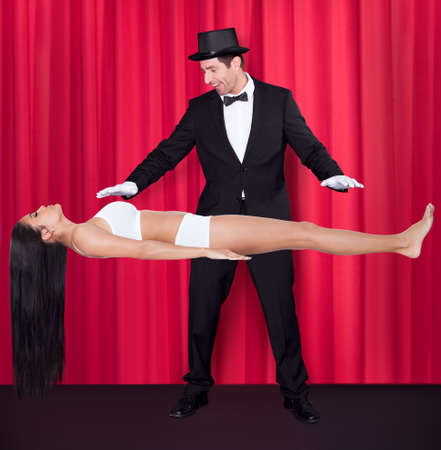 Magician Performs Magic With Beauty Girls In Mid-air Reklamní fotografie