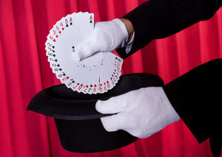Magician Hand Holding Fanned Deck Of Cards From Hat photo