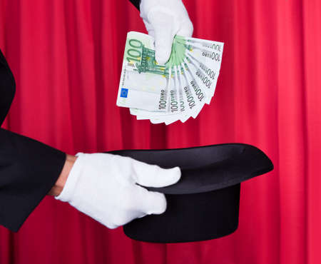 Magician Hand Holding 100 Euro Note From Hat photo