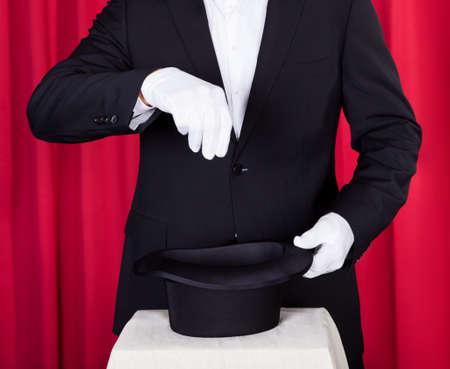 sombrero de mago: Un Mago En Un Juego Negro Que Sostiene Un Sombrero Superior Y Empty Varita m�gica