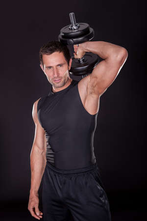 pumping: Young Attractive Man Pumping Weights In A Black Tank Top