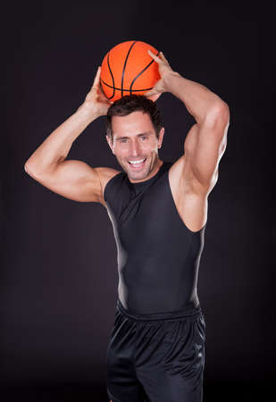 top: Young Man Throwing Basketball Isolated On Black Background Stock Photo