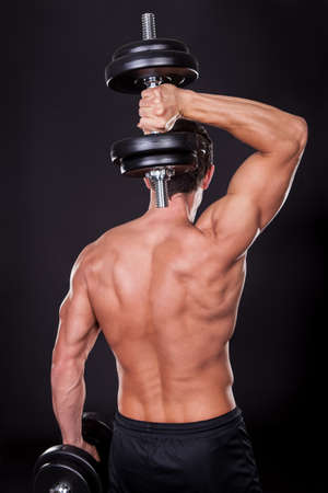 back exercise: Young Man Exercising With Weightlift Isolated On Black Background