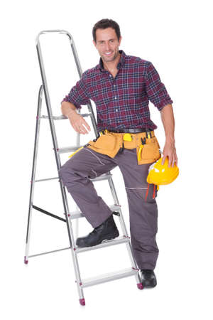 Young Worker Man With Hard Hat Leaning On Ladder photo