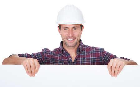 白い背景の上のプラカードを持ってハード帽子をかぶっている男
